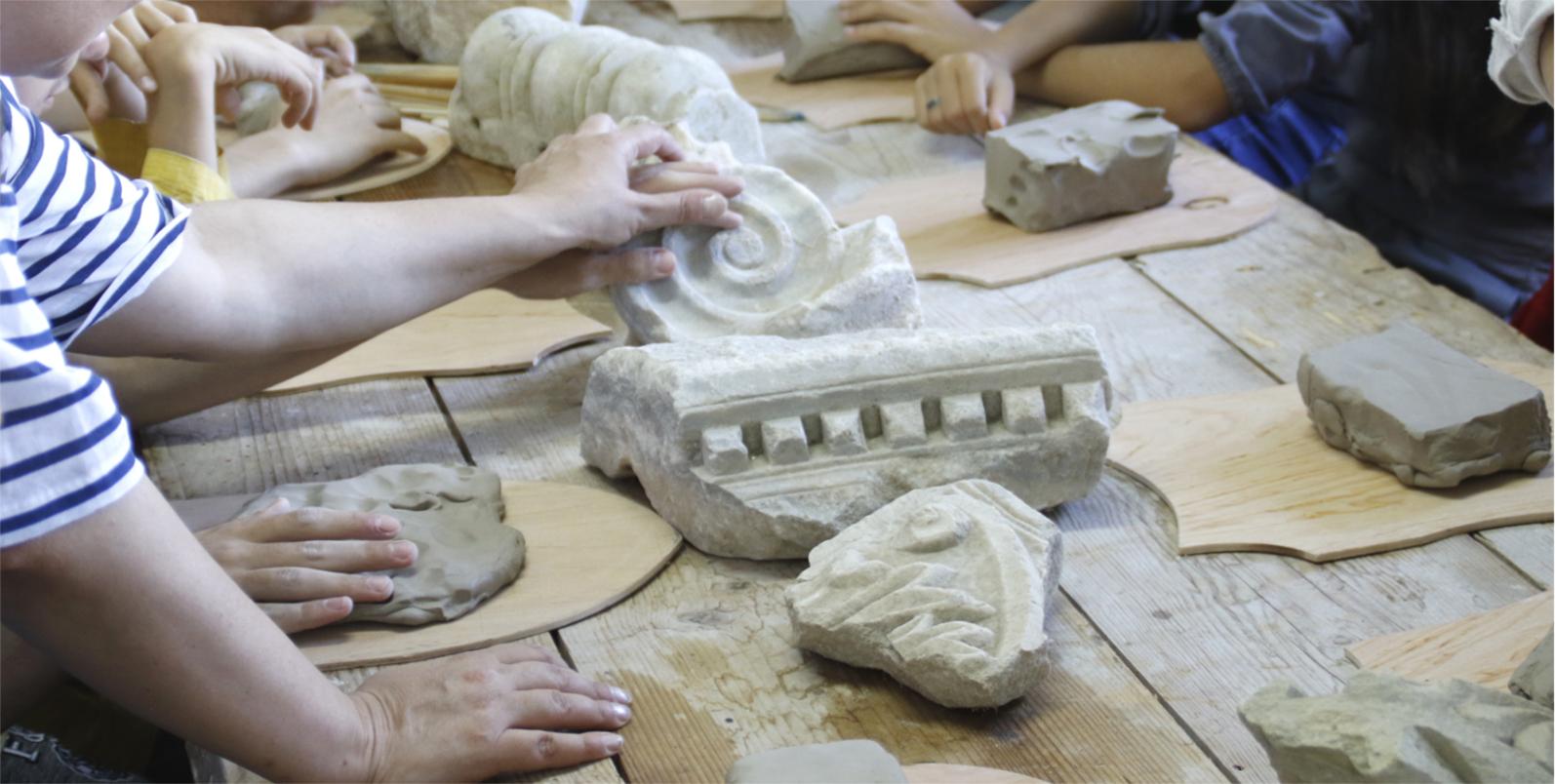 Fotografie cu mainile unor copii care stau în jurul unei mese și studiază istoria într-o manieră tactilă: pipăind și atingând obiecte din lut și din piatră